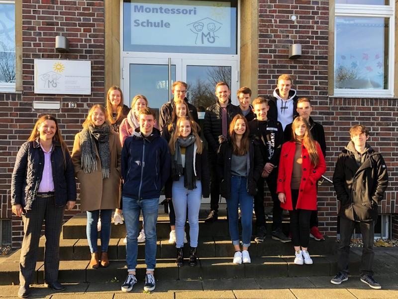 v.l.: Fr. Reglin mit den Oberstufenschülerinnen und -schülern des Erziehungswissenschaftskurses vor der Montessori Grundschule in Coesfeld